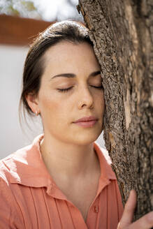 Beautiful woman with eyes closed embracing tree in garden - AFVF08270