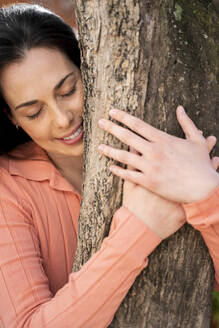 Affectionate woman embracing tree trunk in garden - AFVF08273