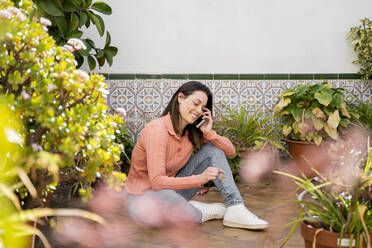 Smiling woman talking on mobile phone while sitting in garden - AFVF08279