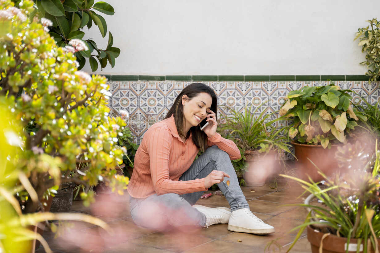 Lächelnde Frau, die mit dem Handy spricht, während sie im Garten sitzt - AFVF08279 - VITTA GALLERY/Westend61