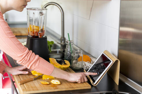 Young woman using digital tablet while preparing fruit smoothie in kitchen - AFVF08288