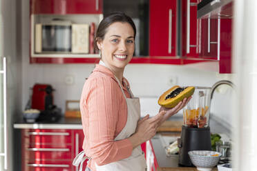 Smiling woman holding papaya while standing in kitchen at home - AFVF08291
