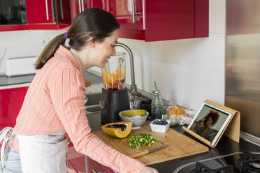 Young woman making healthy fruit smoothie in kitchen. Recipe, videochat, connected, healthy lifestyle, health, fruit, cute, beautiful, stay at home - AFVF08294