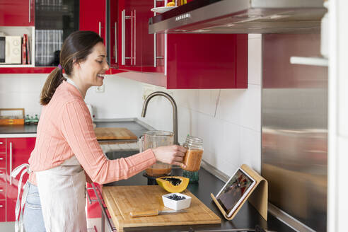 Smiling woman showing smoothie jar to friends on video call while standing in kitchen at home - AFVF08300