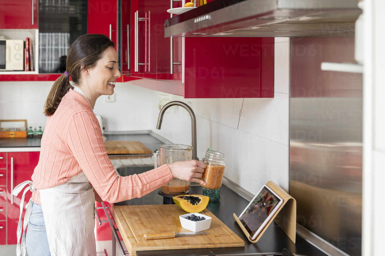 Young woman making healthy fruit smoothie in kitchen. Recipe, videochat, connected, healthy lifestyle, health, fruit, cute, beautiful, stay at home - AFVF08300 - VITTA GALLERY/Westend61