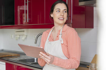 Beautiful woman looking away while holding digital tablet in kitchen at home - AFVF08303