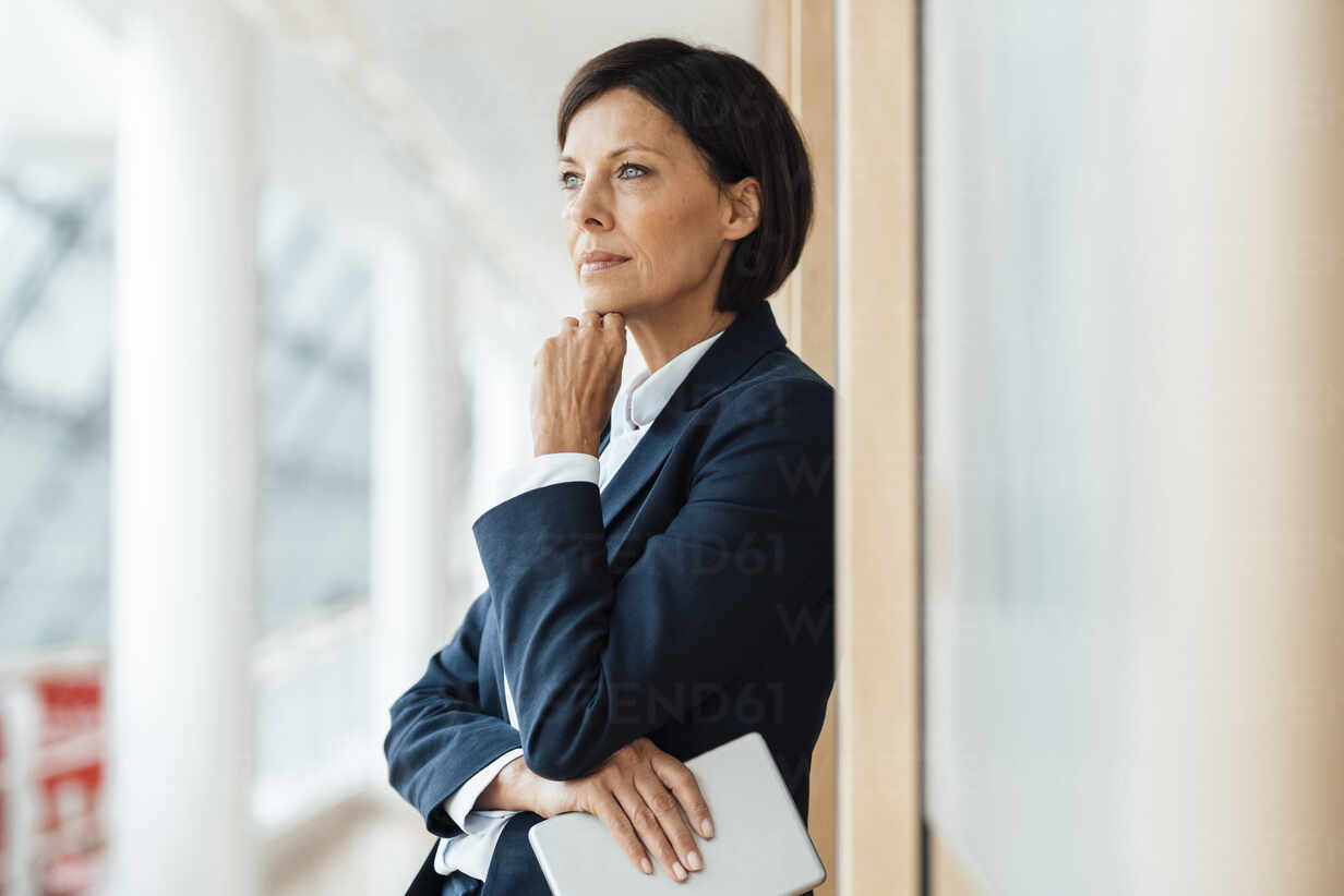 Thoughtful businesswoman with hand on chin against wall in office - JOSEF03615 - Joseffson/Westend61