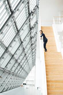 Female entrepreneur standing on steps in corridor - JOSEF03624