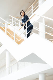 Female entrepreneur with hand on chin contemplating while standing over staircase - JOSEF03630