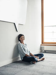 Smiling female entrepreneur sitting on floor in office against wall - JOSEF03636