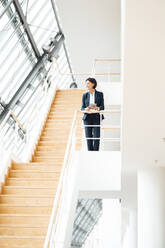 Mature businesswoman with digital tablet standing on steps at office - JOSEF03639