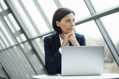 Thoughtful businesswoman with hand on chin by laptop at desk in office - JOSEF03645
