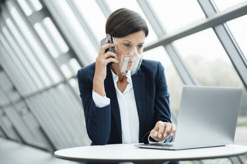 Mature businesswoman talking on smart phone while working in office during COVID-19 - JOSEF03648