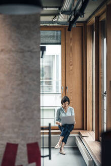 Female entrepreneur working on laptop while sitting over alcove window seat at office - JOSEF03651