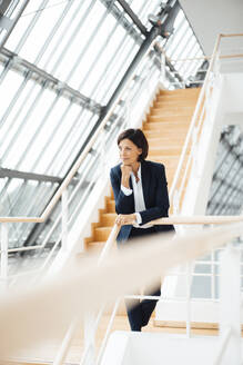 Businesswoman with hand on chin leaning over railing in corridor - JOSEF03654