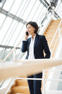 Female entrepreneur talking on smart phone while standing on staircase - JOSEF03657