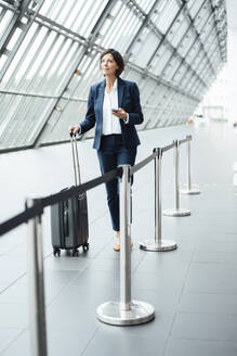 Female professional with smart phone and suitcase walking in corridor - JOSEF03663