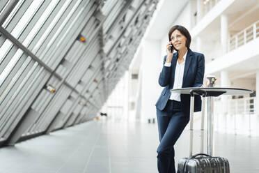 Female entrepreneur with coffee cup talking on smart phone in corridor - JOSEF03666