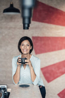 Smiling businesswoman with coffee cup in office - JOSEF03672