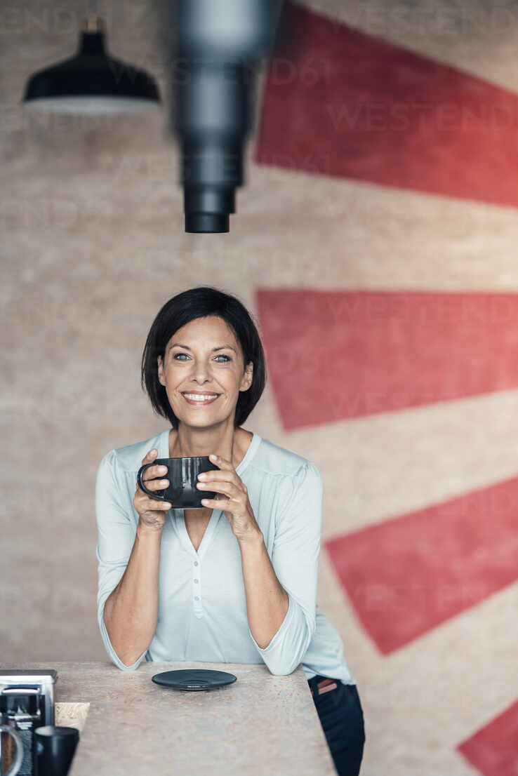 Smiling businesswoman with coffee cup in office - JOSEF03672 - Joseffson/Westend61