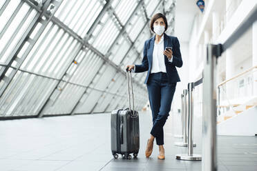 Businesswoman with smart phone and suitcase standing in corridor during COVID-19 - JOSEF03675
