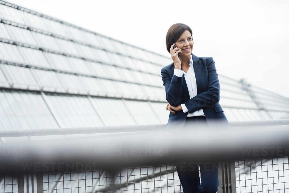 Weibliche Unternehmerin spricht auf Smartphone außerhalb Bürogebäude - JOSEF03693 - Joseffson/Westend61