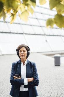 Businesswoman with arms crossed listening music outside office - JOSEF03696