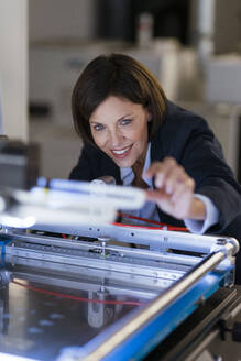 Smiling businesswoman examining machinery at illuminated factory - JOSEF03702
