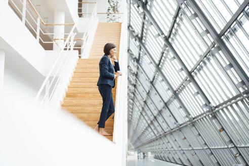 Female professional standing on steps in corridor - JOSEF03705
