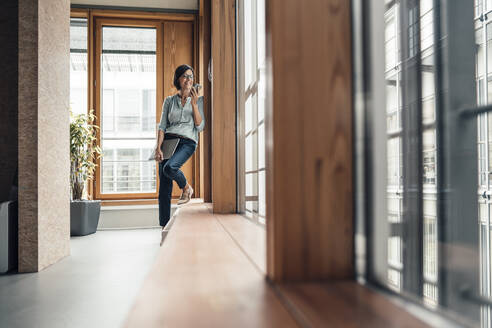 Mature businesswoman with smart phone standing by window at office - JOSEF03714