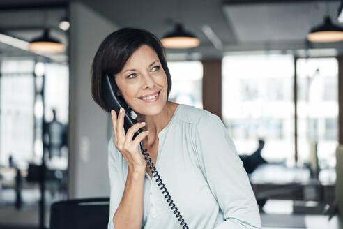 Female entrepreneur talking on telephone at office - JOSEF03717