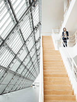 Female professional standing by railing over steps at office - JOSEF03735