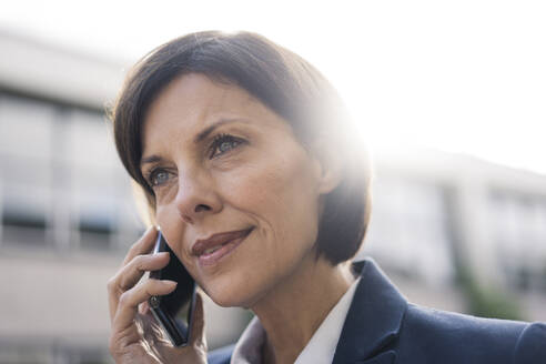 Mature businesswoman talking on smart phone outdoors - JOSEF03741