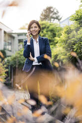 Smiling businesswoman talking on smart phone in office park - JOSEF03747