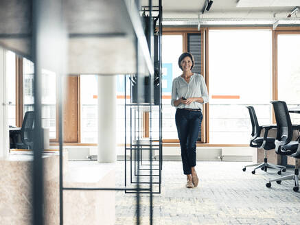 Happy female entrepreneur with smart phone standing at office - JOSEF03753