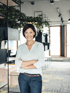 Confident businesswoman with arms crossed at office - JOSEF03756