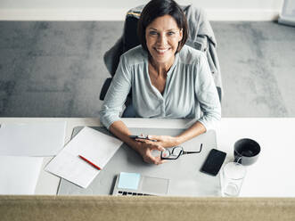 Smiling female entrepreneur sitting on chair at desk in office - JOSEF03759
