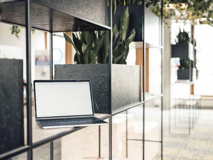 Laptop on rack in office - JOSEF03765
