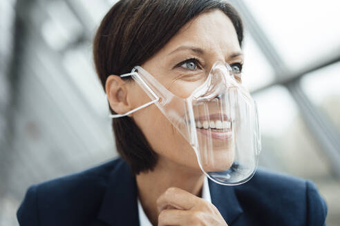 Mature businesswoman with protective face shield at office - JOSEF03774