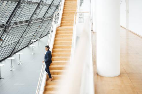 Female professional standing on steps in corridor - JOSEF03786