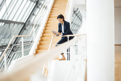 Businesswoman using digital tablet while leaning on railing in corridor - JOSEF03789