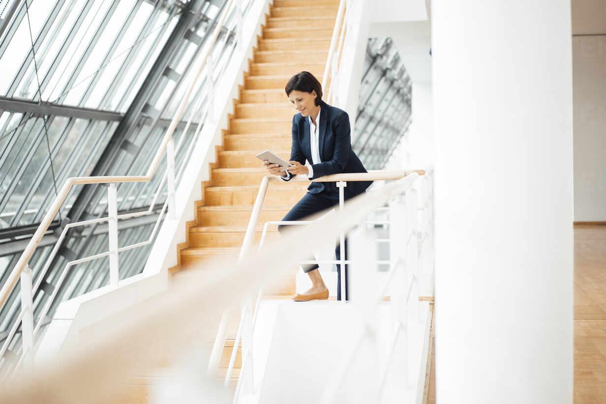 Businesswoman using digital tablet while leaning on railing in corridor - JOSEF03789 - Joseffson/Westend61