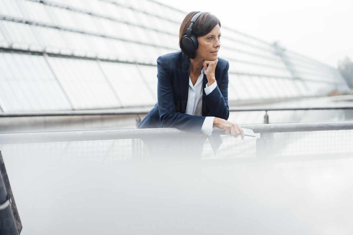 Weibliche Unternehmerin hört Musik, während sie sich an ein Geländer außerhalb eines Bürogebäudes lehnt - JOSEF03798 - Joseffson/Westend61