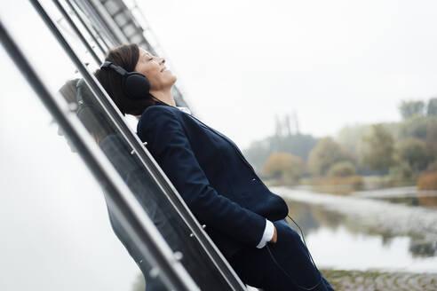 Mature businesswoman with hand in pocket listening music through headphones at lakeshore - JOSEF03801