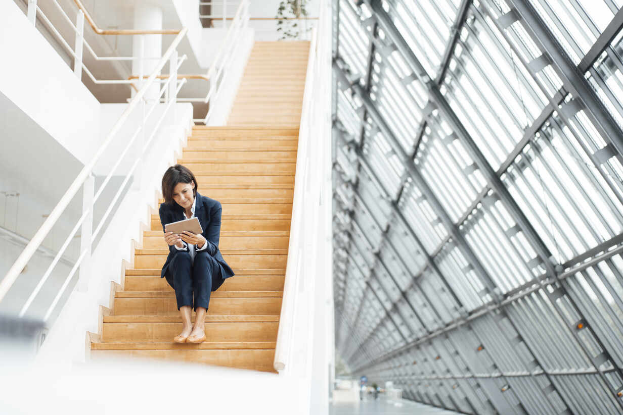 Weiblicher Unternehmer, der ein digitales Tablet benutzt, während er auf einer Treppe im Korridor sitzt - JOSEF03807 - Joseffson/Westend61
