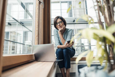 Female entrepreneur with smart phone looking away while sitting in office - JOSEF03813