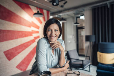 Smiling businesswoman leaning on table at office - JOSEF03816