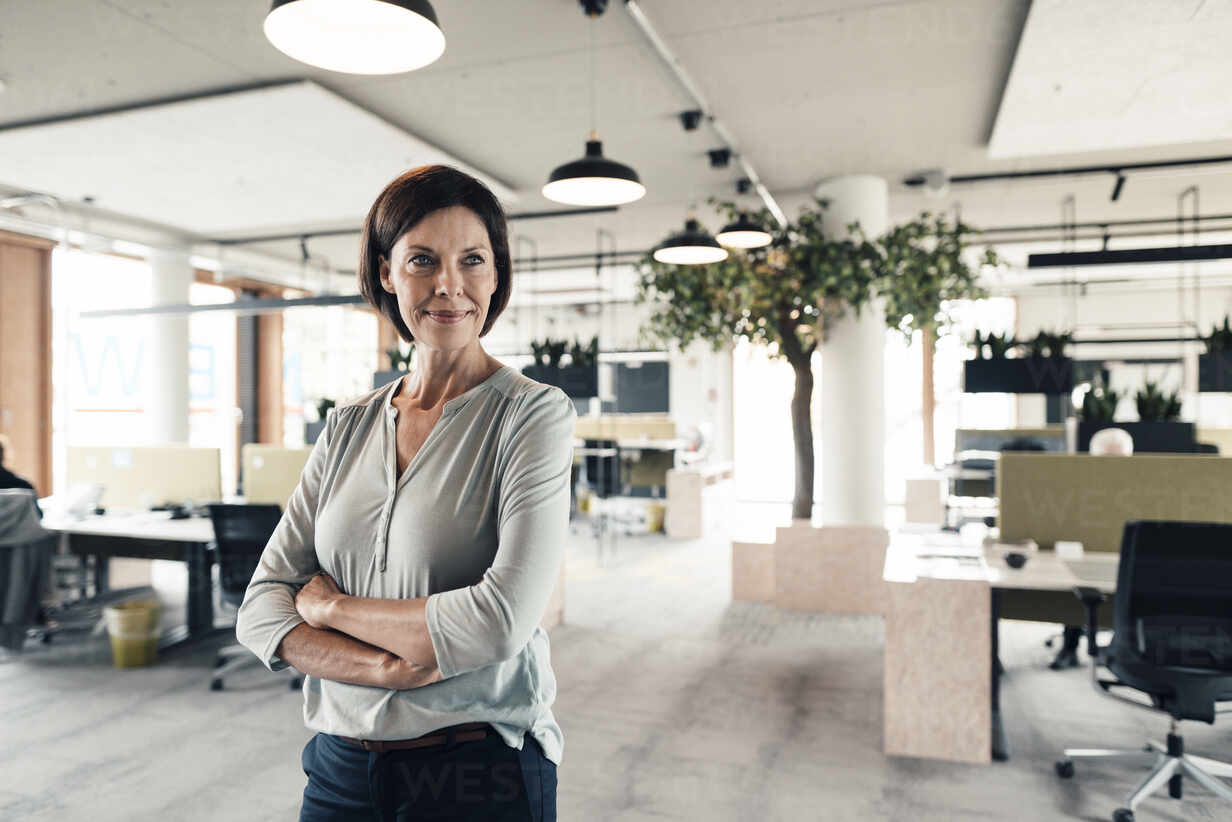 Confident businesswoman with arms crossed looking in office - JOSEF03828 - Joseffson/Westend61