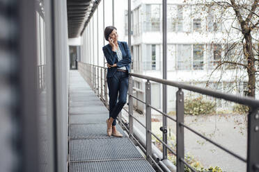 Businesswoman talking on mobile phone while standing on balcony at office - JOSEF03831