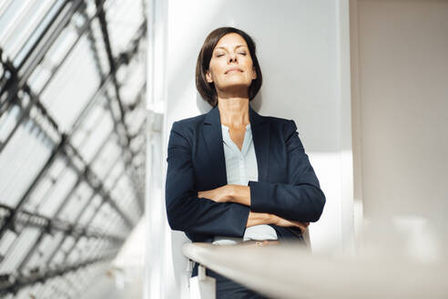Female professional with arms crossed against wall in corridor - JOSEF03837